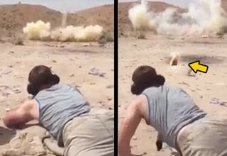 man laying down shooting a rifle and huge piece of rock almost hits him