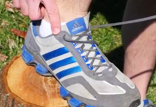guy pointing to extra shoelace hole in addidas shoes
