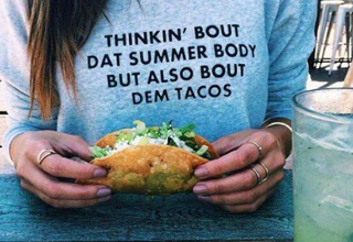 Woman holds a taco and wears a sweater about eating it.