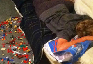 kid sleeping with legos on the ground