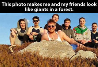 guys posing by a rock and photo looks like they are giants in a tiny forest