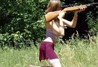 girl with her eye on the scope of a shotgun
