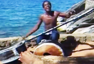african man playing drum guitar instrument in front of the ocean