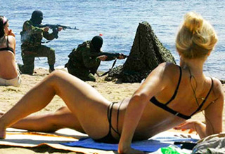 girl in bikini on beach guys with guns drawn in the backround