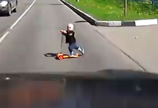 little kid riding scooter across busy street