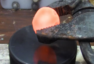pliers placing a red hot nickel ball onto a hockey puck