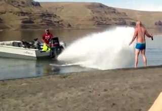 man driving boat knocks beach goer over with engine spray