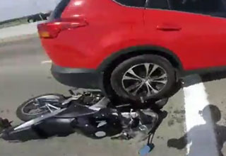 red suv backing over a motorcycle