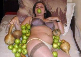 girl in lingere trying to be sexy but posing with fruit and vegetables