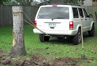 suv trying to pull stump