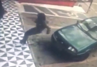 woman falls after trying to sit on a car hood thats backing up