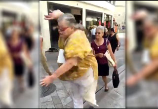 elderly woman falling on a crowded sidewalk