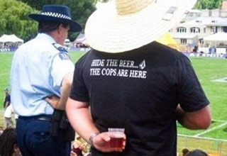 man wearing hide the beer shirt hiding beer from cops