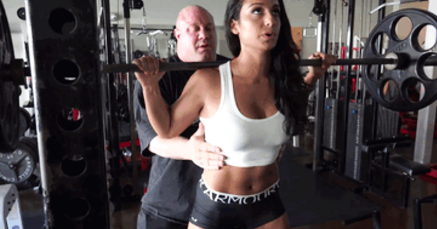 girl doing squats with guy spotting