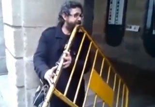 man holding barrier and playing it like a flute