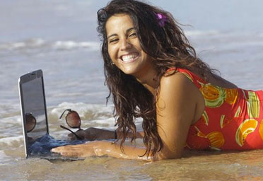 woman laying in ocean with laptop