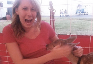 funny picture of woman freaking out with a baby deer biting her shirt