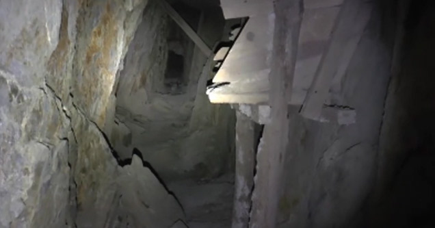 a photo of a narrow cave shaft with a flashlight shining down it