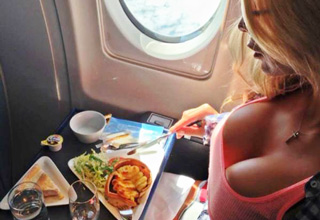 woman with ample cleavage eating a healthy meal on an airplane - cover for Sheer Awesomeness article
