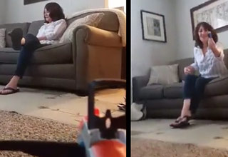 woman sitting on couch son hiding with toy gun aimed at her