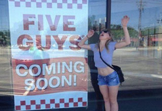 Funny picture of a girl making funny gestures in front of sign for Five Guys - Cover for WTF and funny images