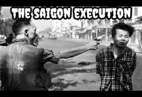 a Vietnamese man holding a gun at a prisoner