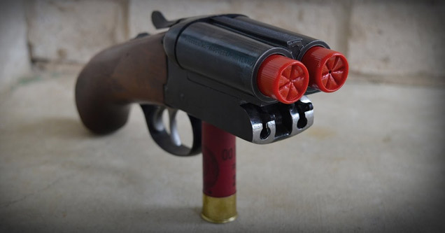 tiny double barrell shotgun sitting on a shotgun shell