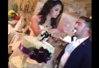 newly wed couple eating cake at wedding