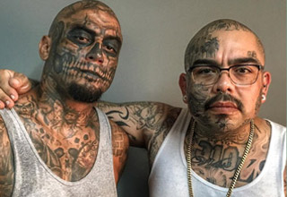 two men covered in tattoos pose for a photo