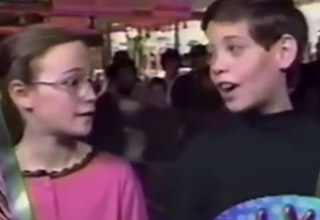 a young girl in pink shirt wearing glasses talks o a young boy
