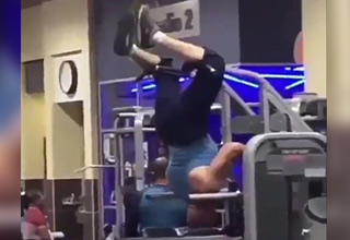 man using machine at gym upside down