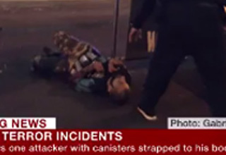 man laying on ground with explosives strapped to him