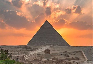 pyramid with sun setting behind it
