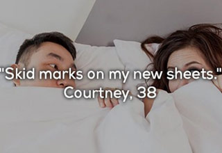 couple laying in bed under the sheets