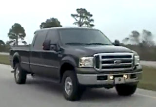 a black ford truck on the freeay