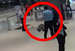 old man lying on the floor after being pushed by airport employee