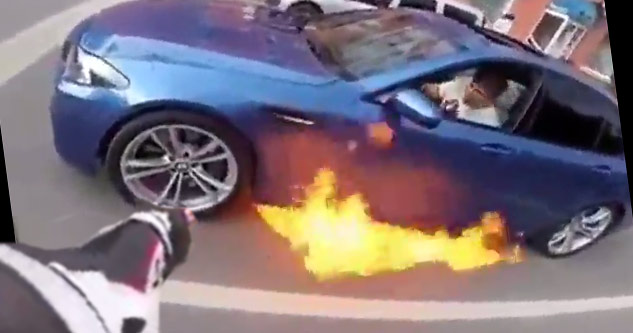biker pointing at car on fire