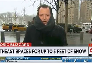 a cnn weatherman standing out in the snow looking cold and sad