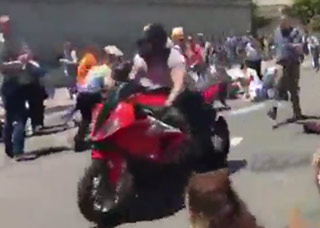 man on red motorcycle rides through crowded street