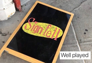 Sign on the ground in Seinfeld font that says Sign Fell