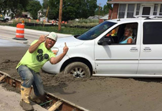 a construction worker flipping off woman who drove through cement