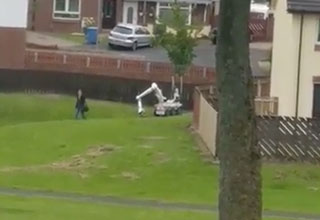 woman walking past bomb disposal robot