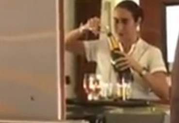flight attendant putting champagne back into bottle