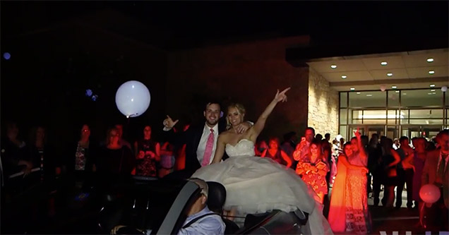 Bride and Groom sitting at the back of a convertible, about to fall off backwards