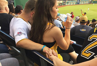 guy with his arm around girl at game holding hands with other girl