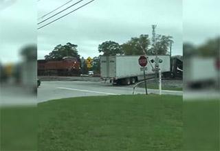 Train plows into semi truck stuck on the tracks
