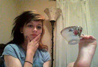 girl holding tea cup with her foot