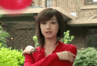 asian girl attempting to catch red ball