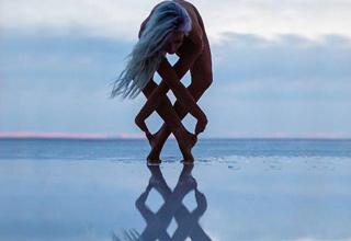woman in yoga pose on reflective lake