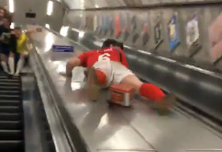 guy sliding down escalator about to hit his crotch